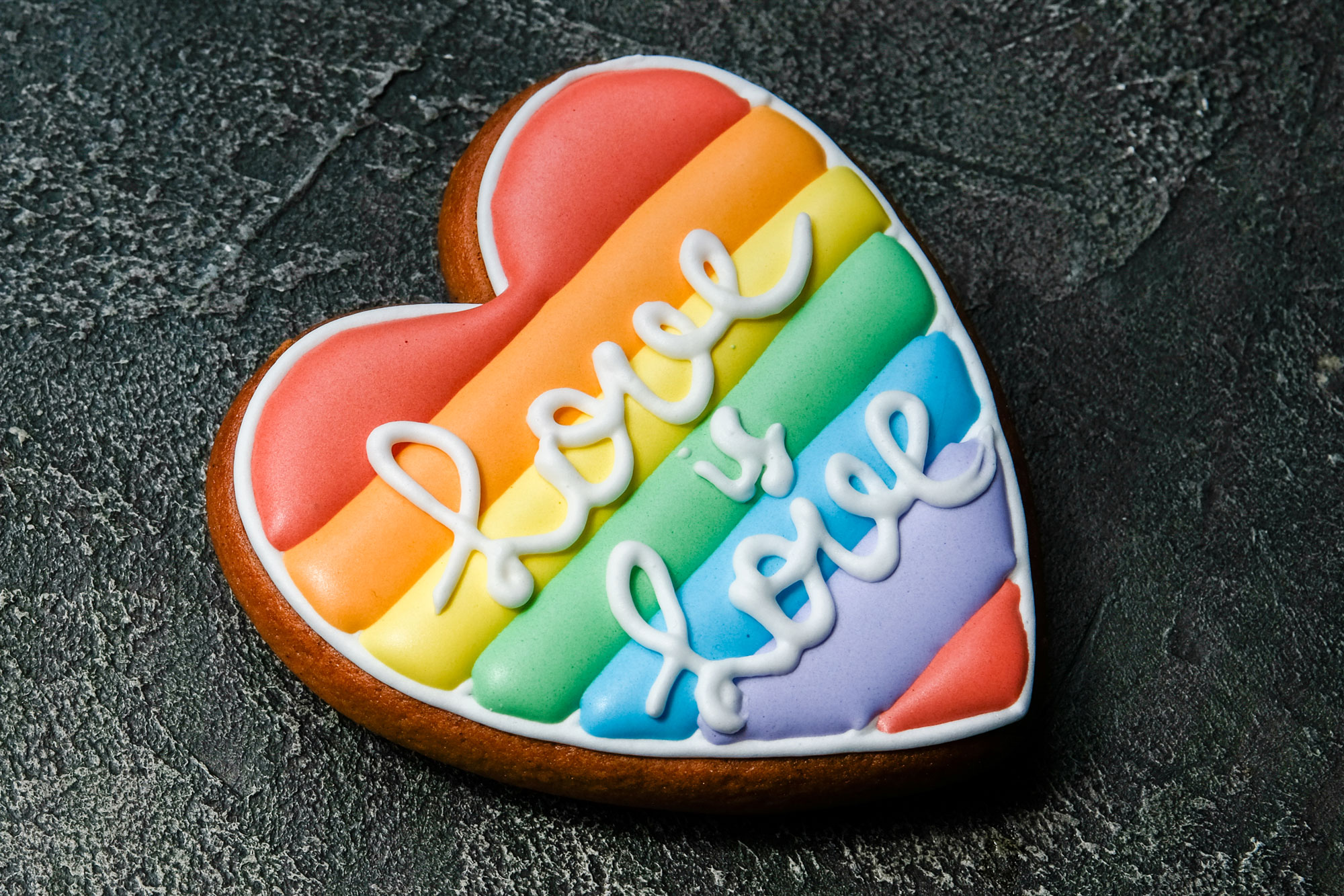"""Rainbow heart cookie with the words """"love is love"""" in icing"""