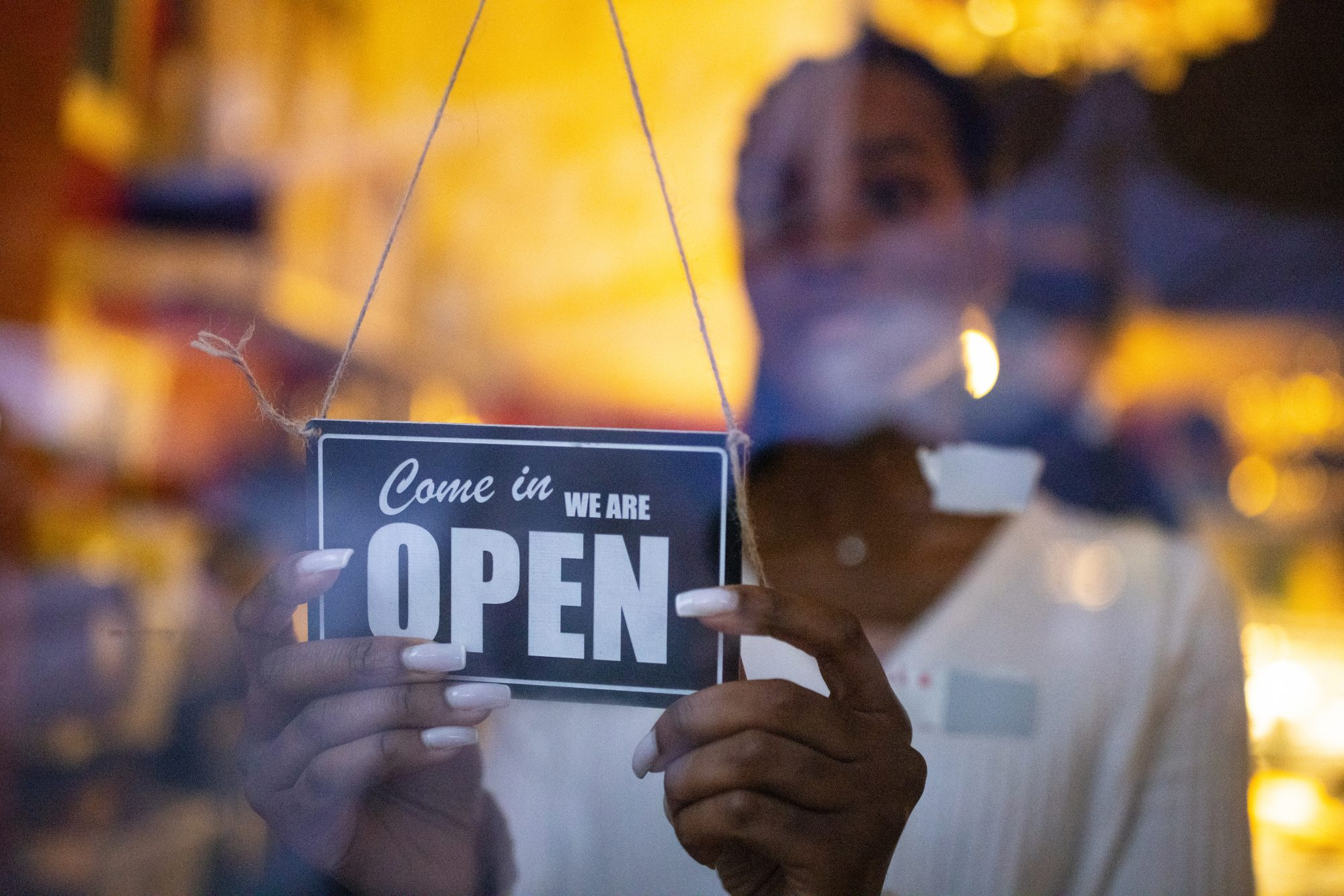 Business owner hanging an open sign at a cafe