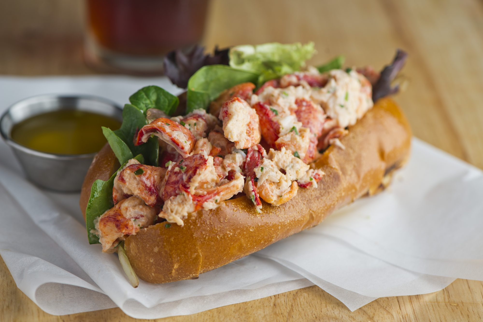 Lobster roll. Maine lobster mixed with mayo, celery, onions, garlic, scallions, chives, lemon juice. Lobster roll on toasted hotdog bun w/ lettuce, tomato, garlic mayo seasoned salt & pepper. Classic American restaurant or diner lunch sandwich favorite.