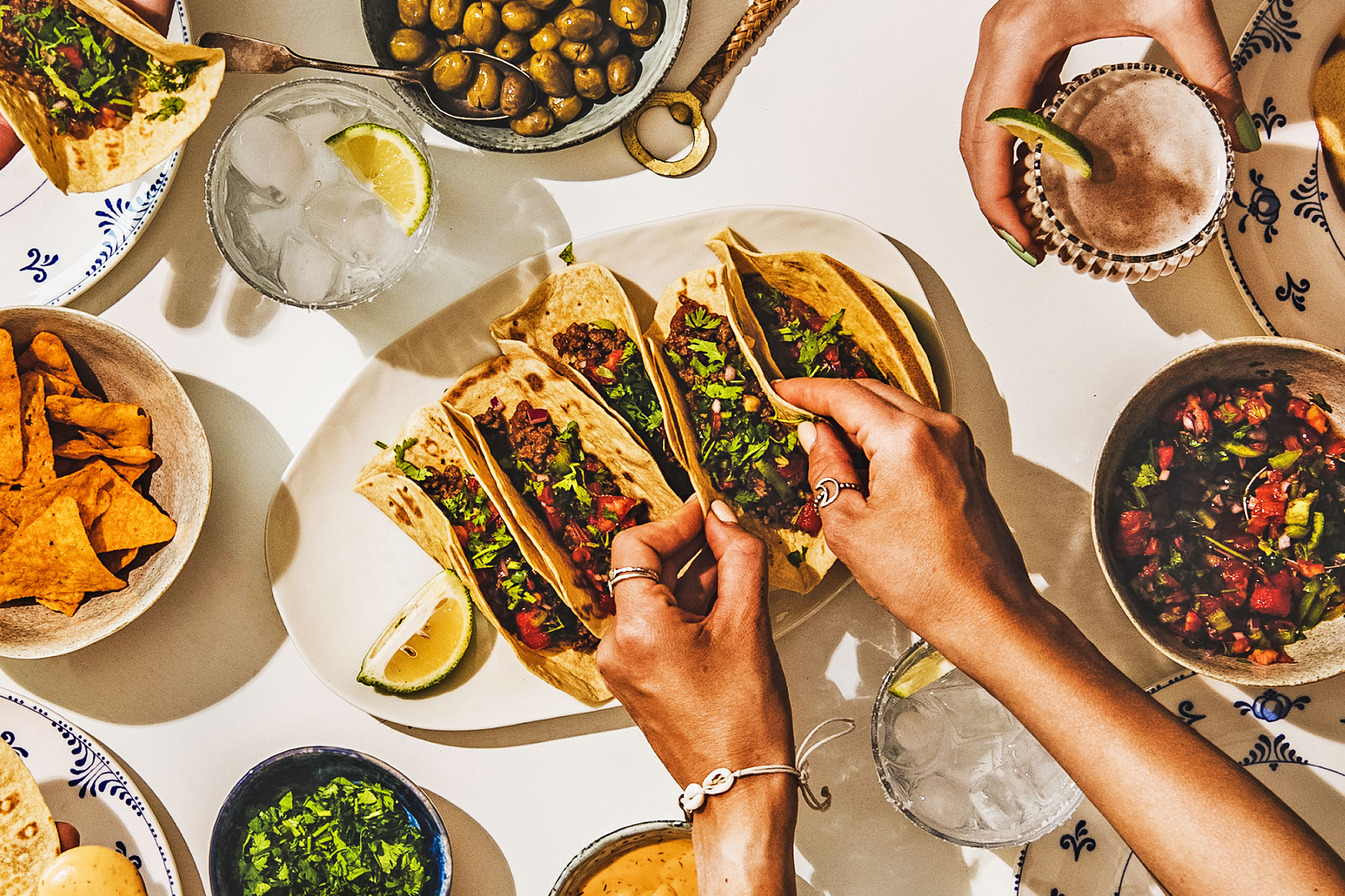 Flat-lay of beef tacos, tomato salsa, tortillas, beer, nachos and peoples hands over white table, top view