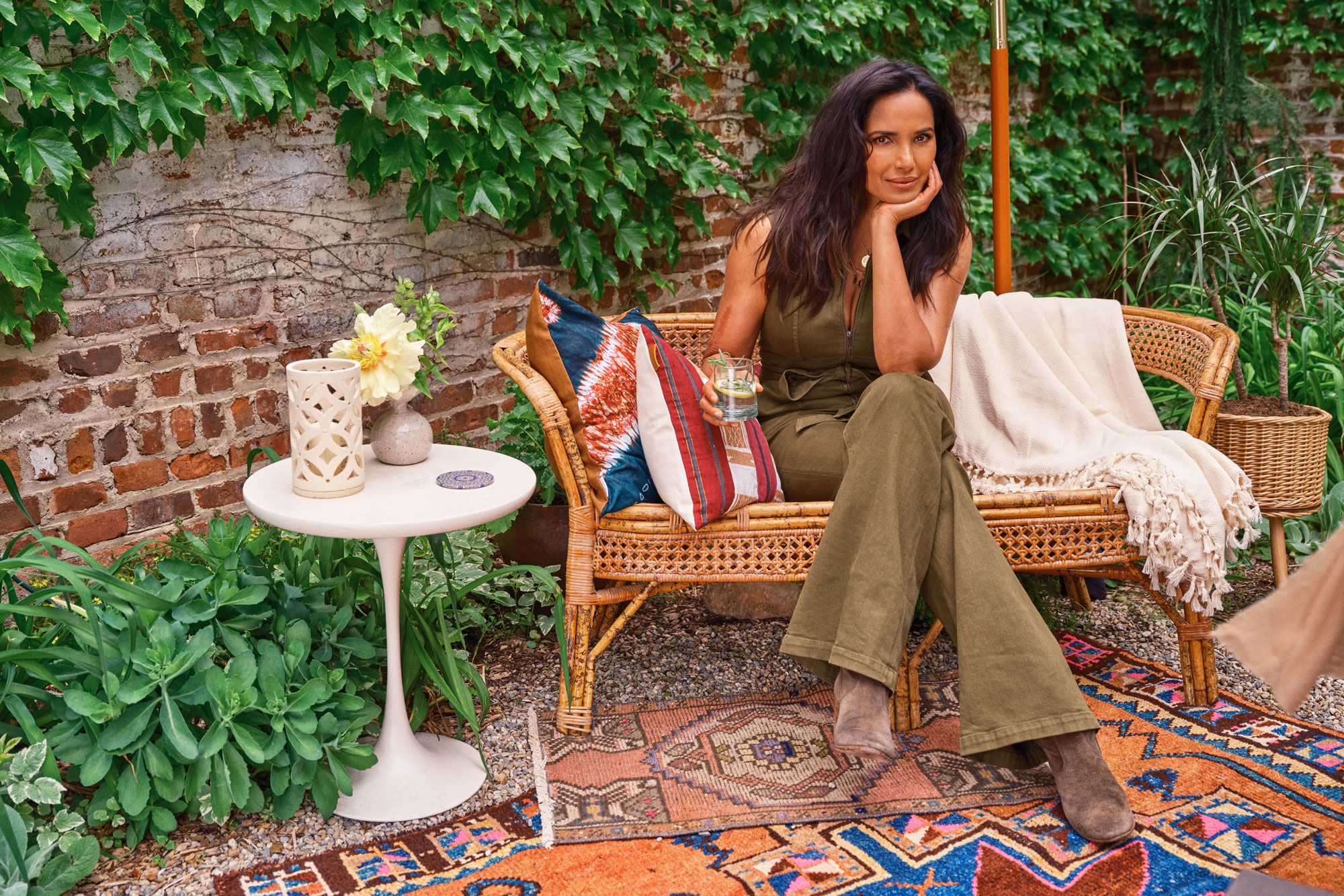 Padma Lakshmi with cocktail on an outdoor couch