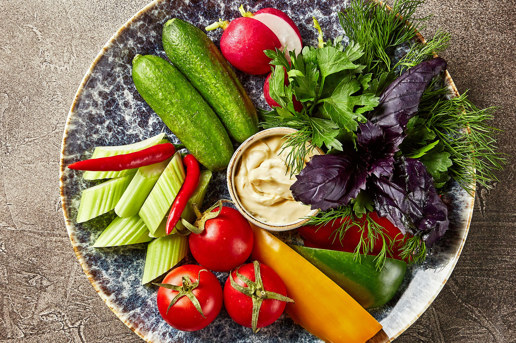 Plate with tomatoes, sweet bell pepper, radish and celery, parsley, dill, cilantro, green onion, red basil on brown background, top view