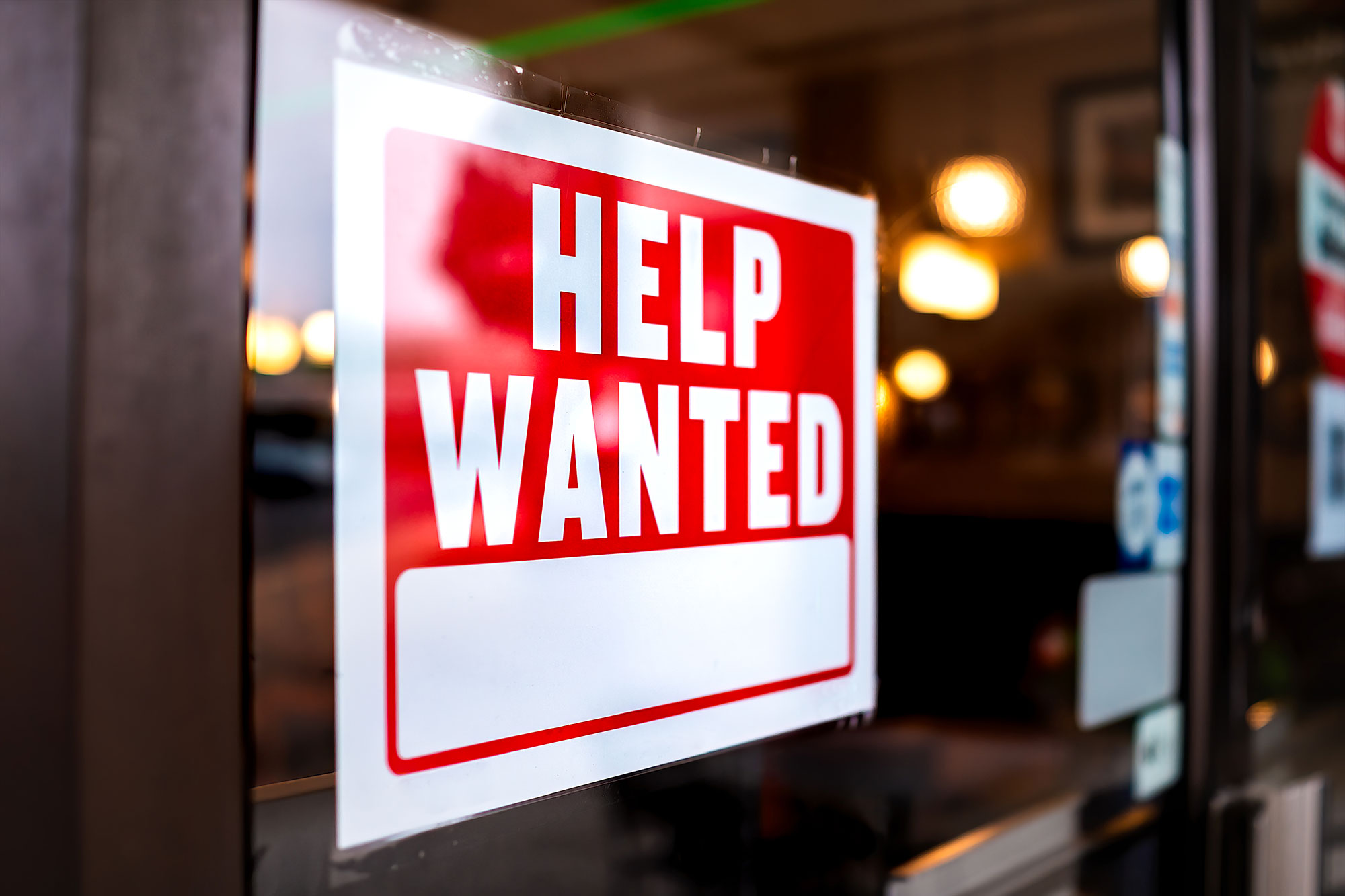 """""""Help Wanted"""" sign in restaurant window"""