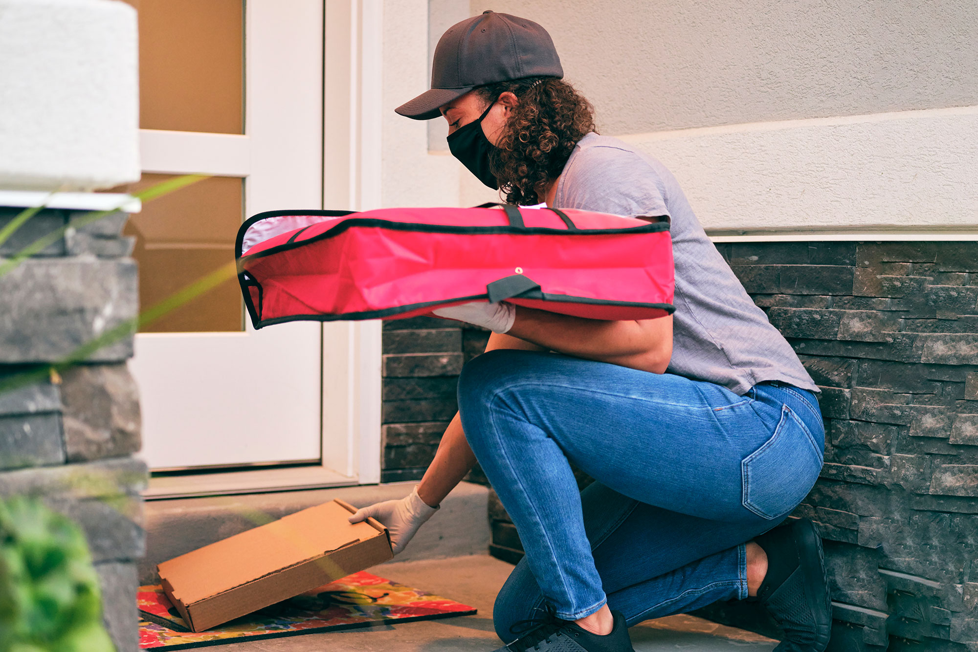Pizza delivery woman dropping off a pizza