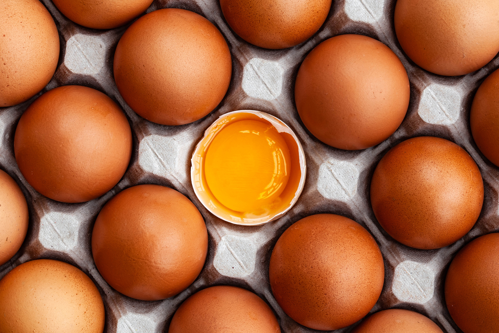 Whole brown chicken eggs and one broken egg in tray