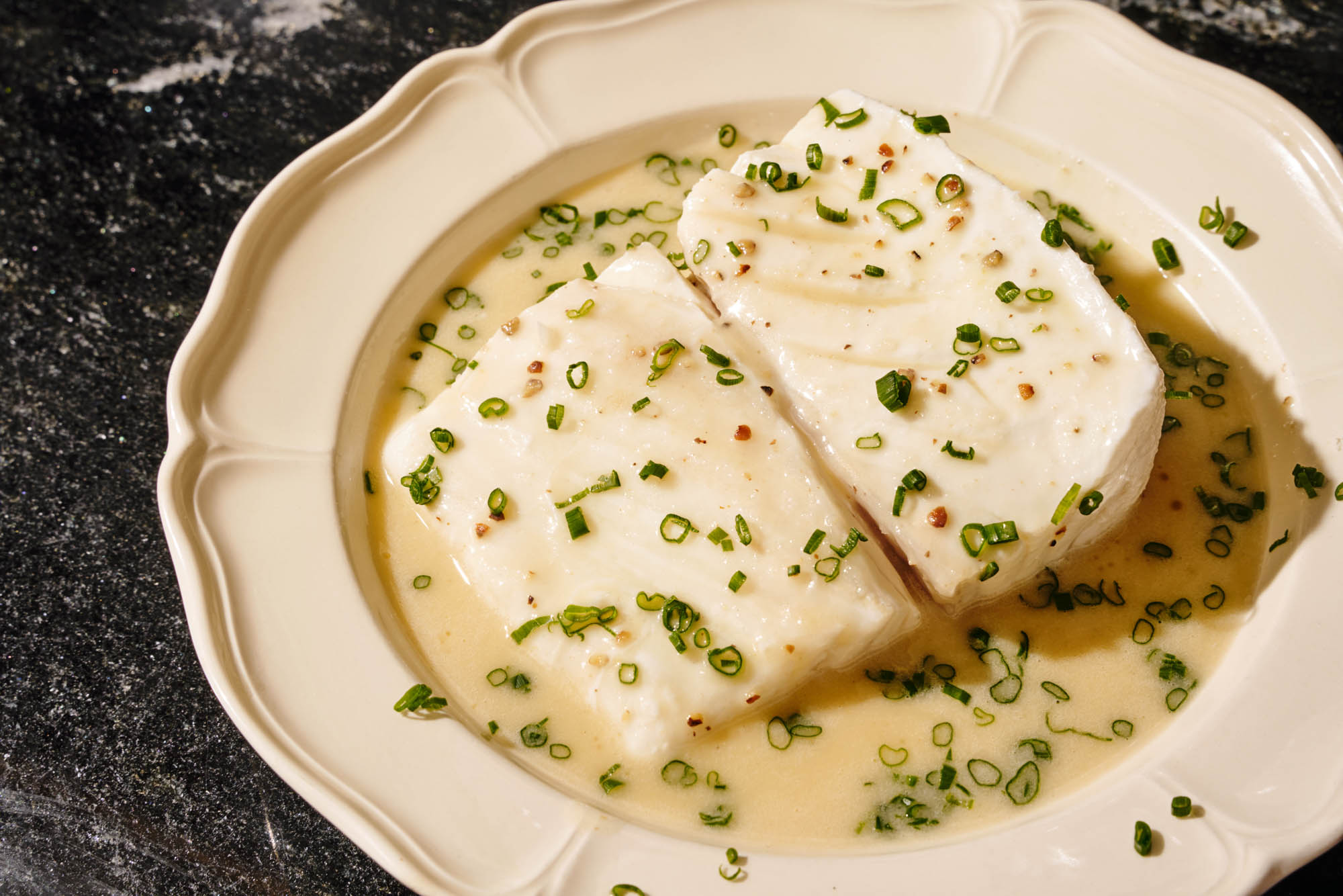 Poached halibut with butter sauce and thinly sliced chives