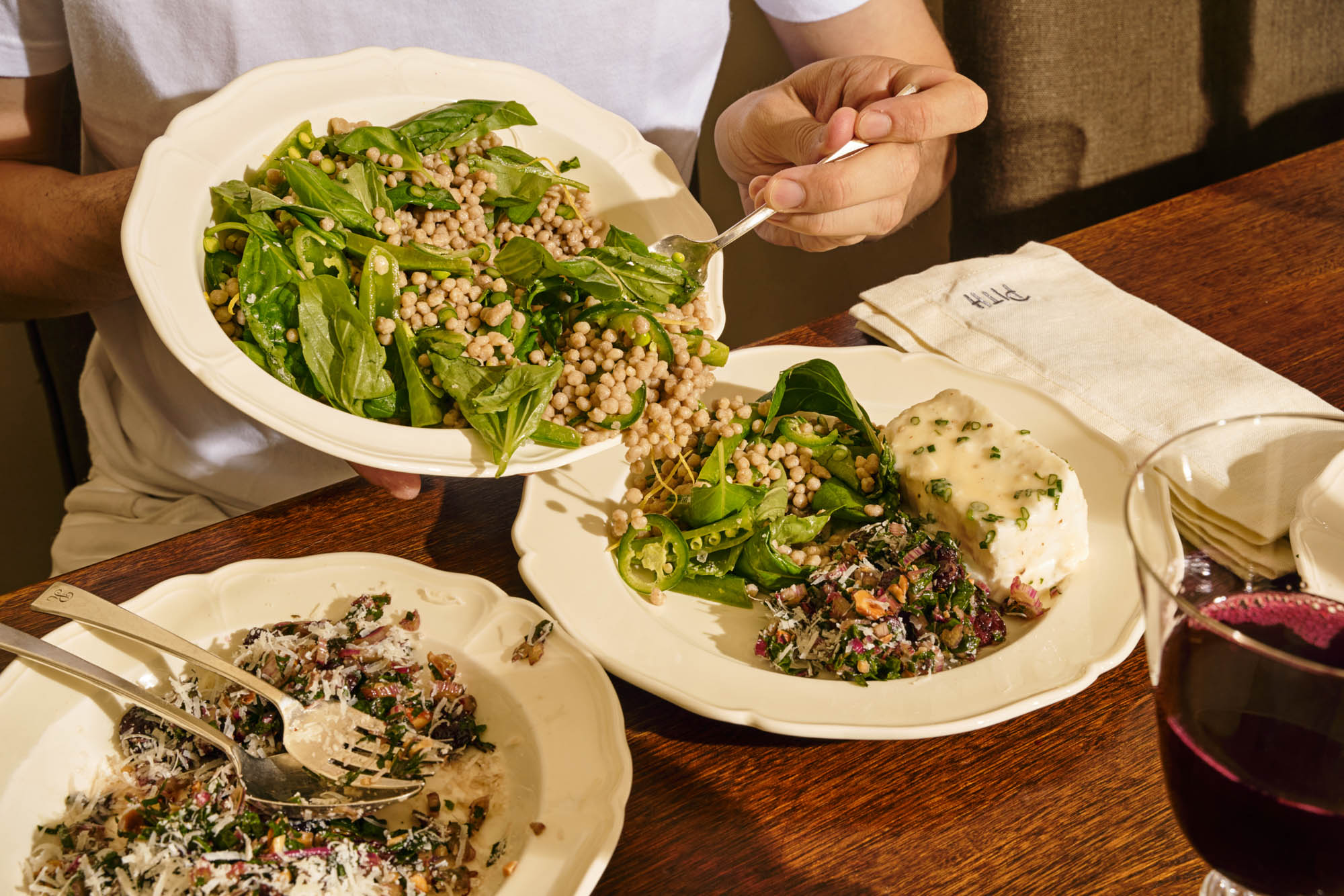 serving grain salad onto a plate with chard salad and poached halibut