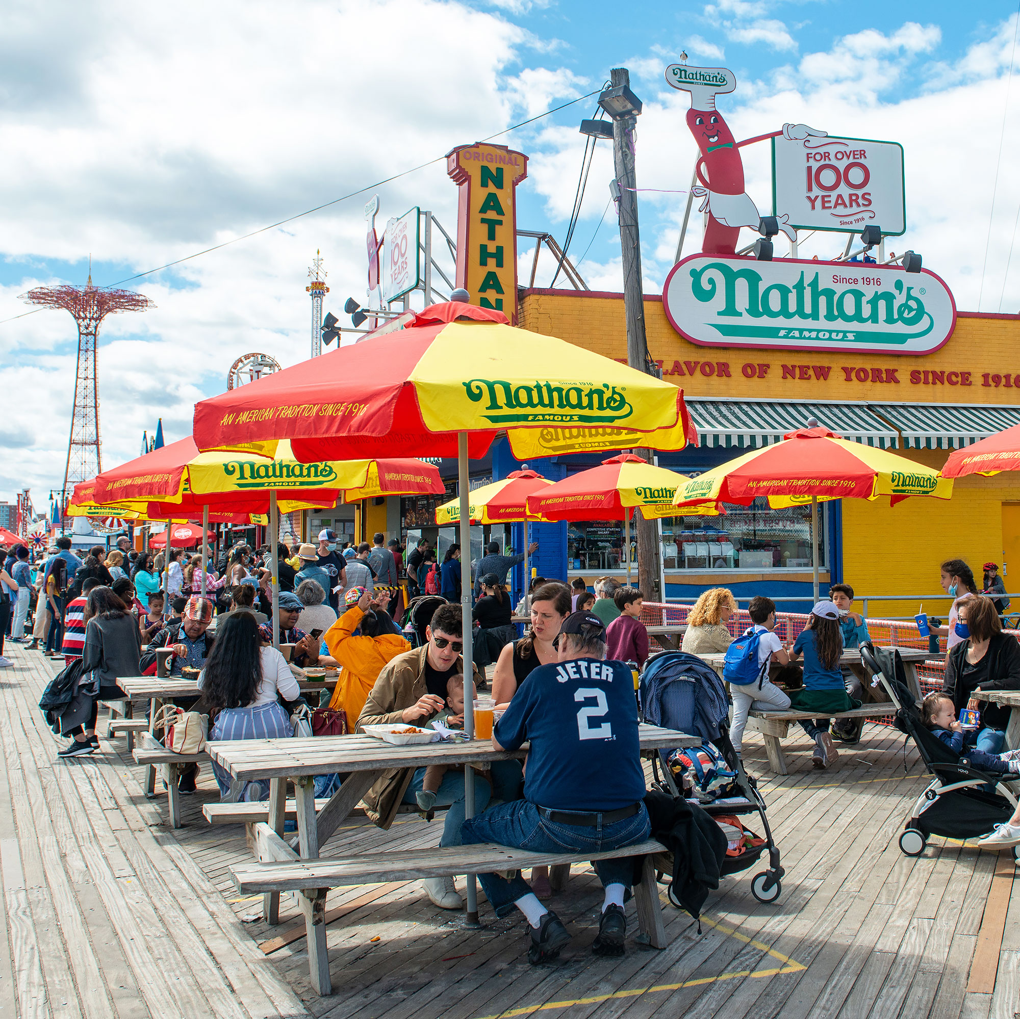 People sit at Nathan's Famous on the boardwalk at Coney Island