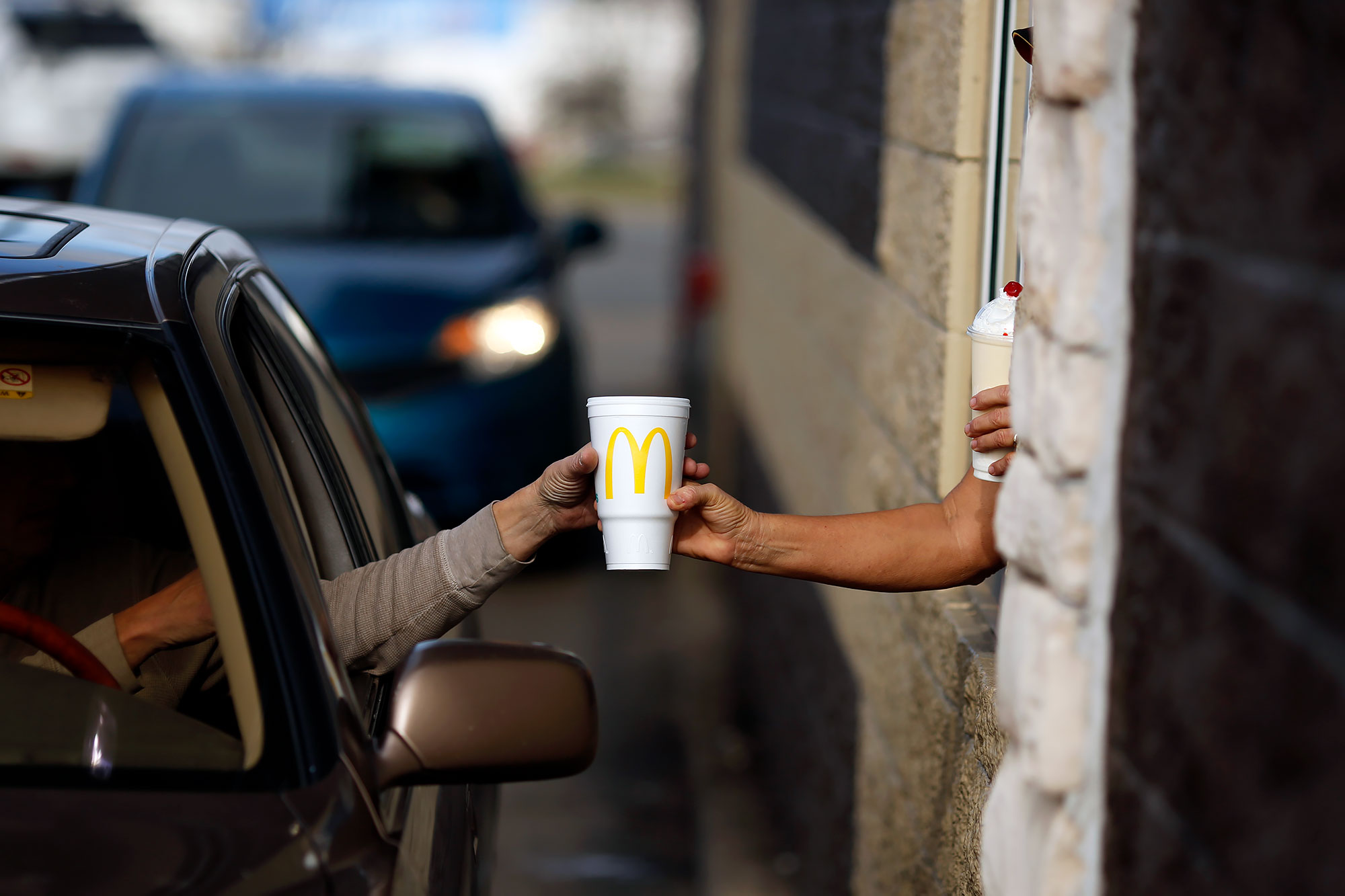 A worker passes a beverage to a customer at the drive-thru window at a McDonald's fast food restaurant