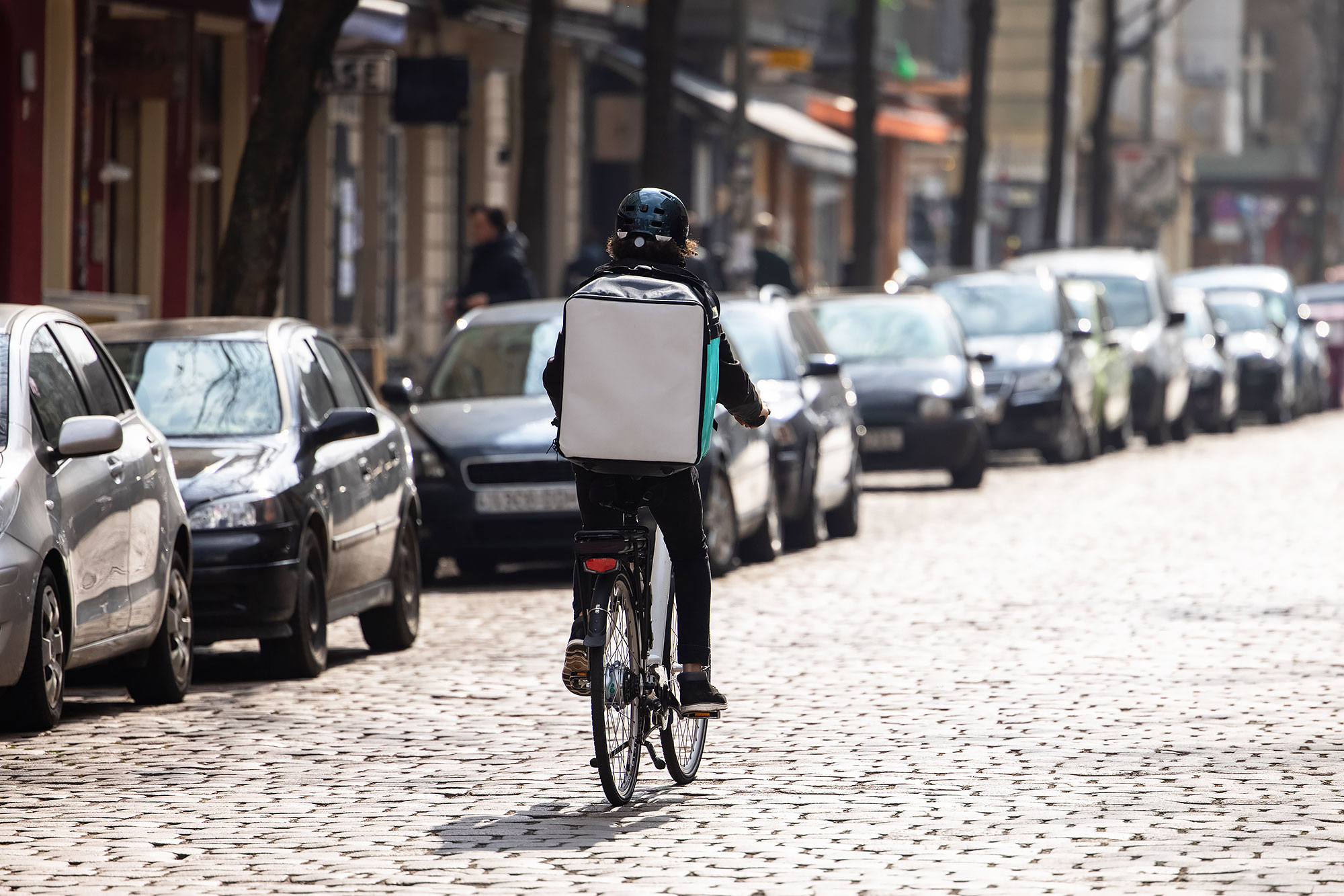 A food delivery person with a thermal backpack riding a bike on the street