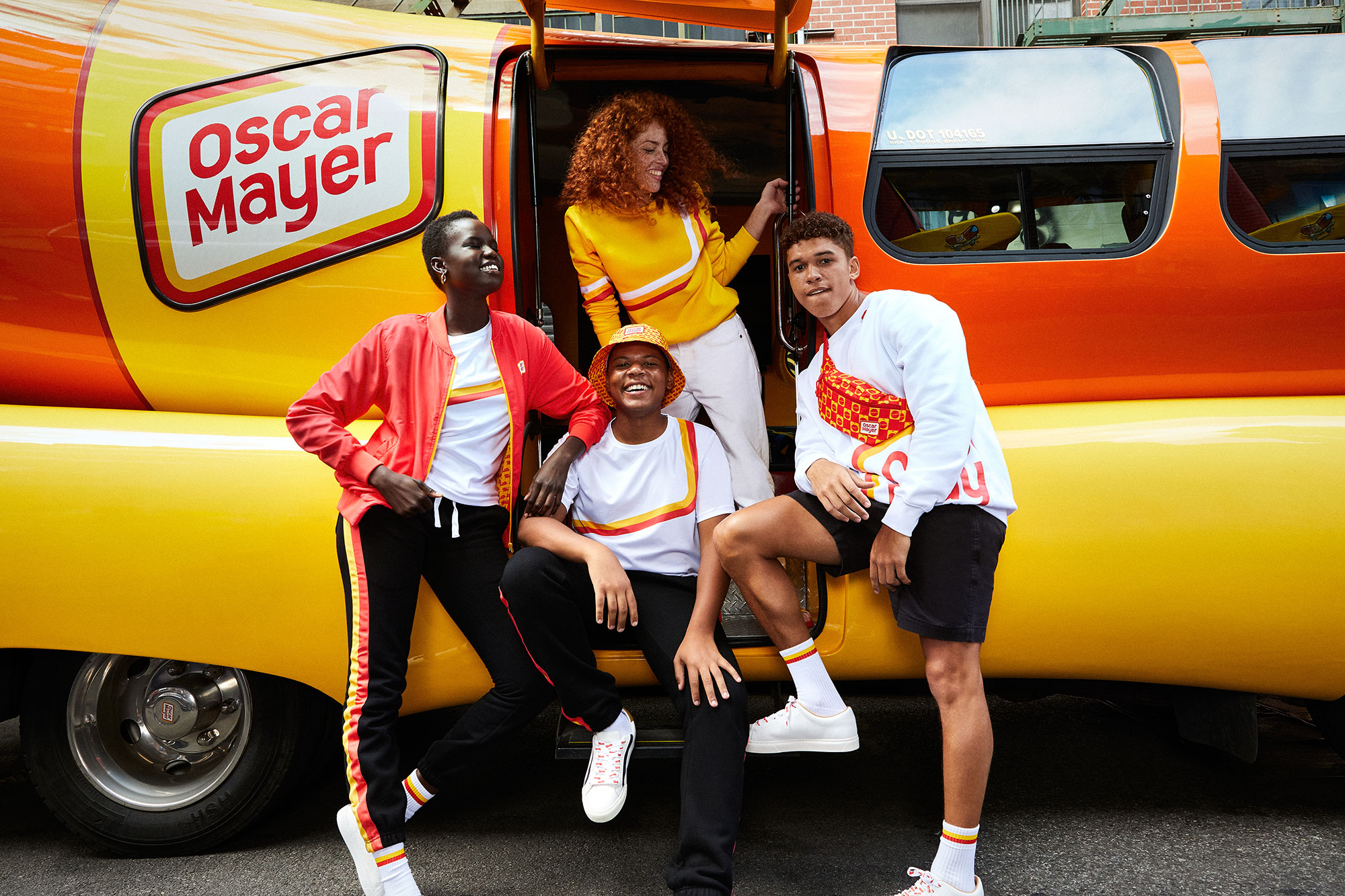 Models wear the Oscar Mayer Street Meat capsule collection outside of an Oscar Meyer hot dog bus