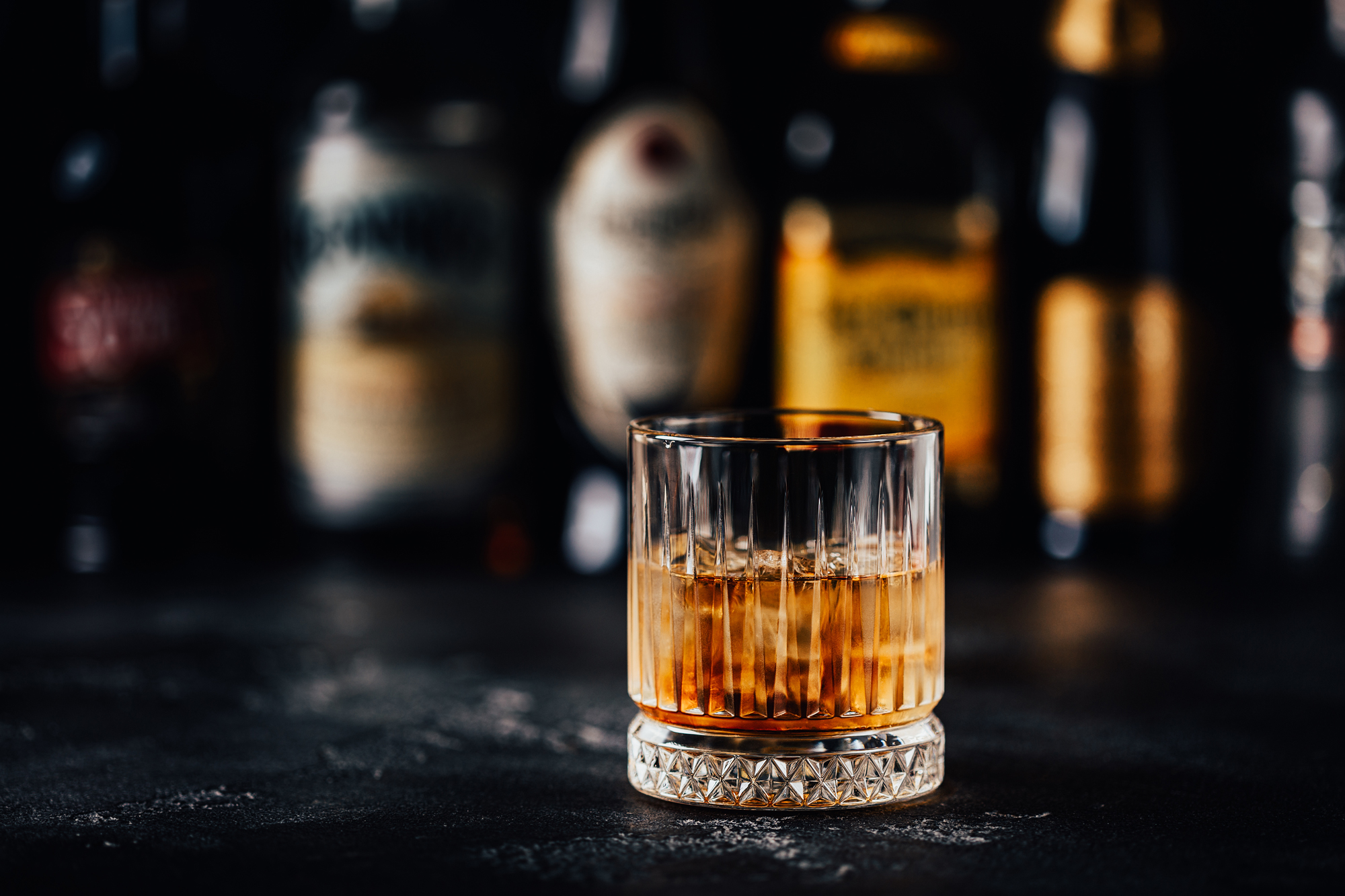 Whiskey with ice on a dark table against the background of bar bottles