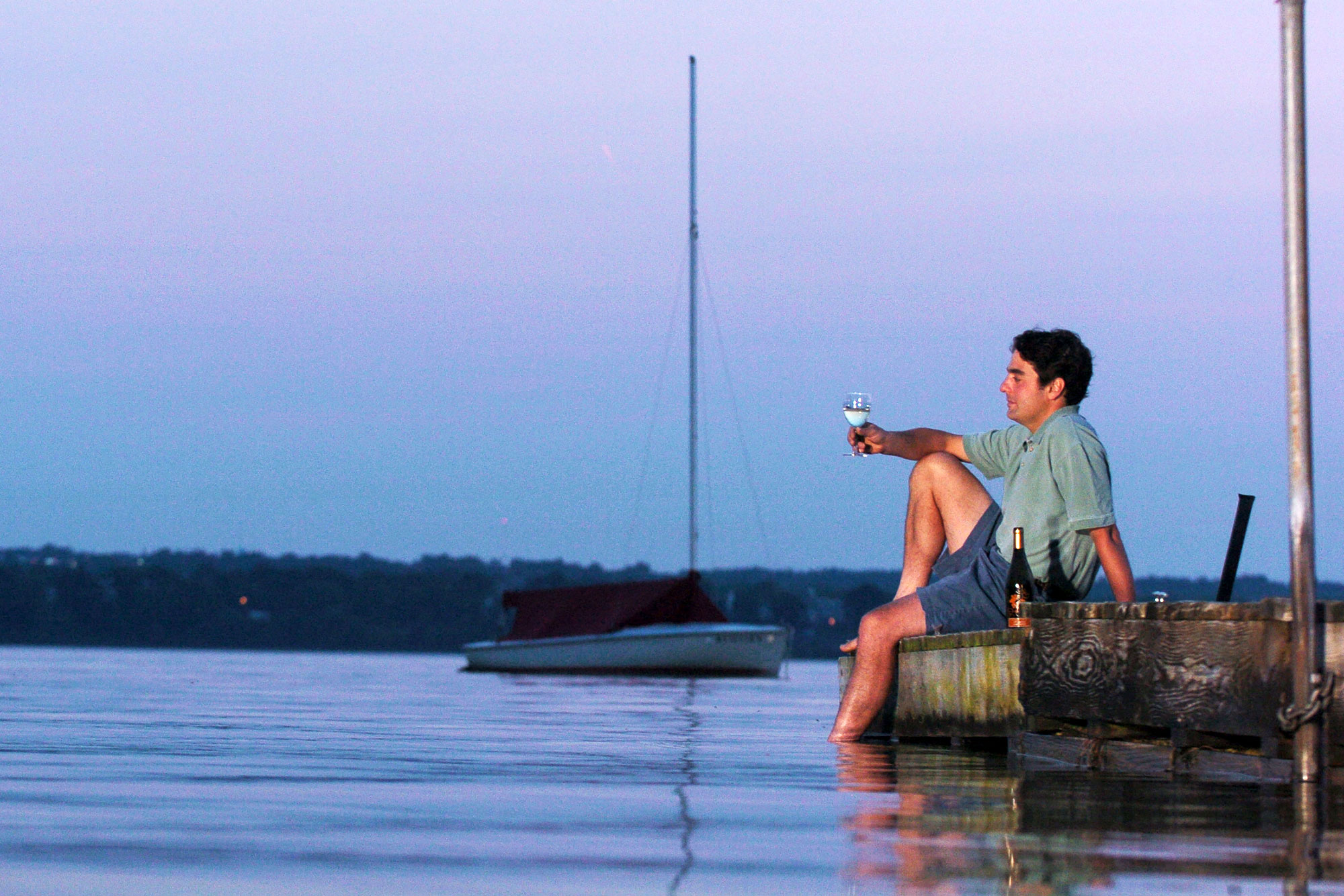A man enjoys wine while sitting on lake's dock in the Finger Lakes region