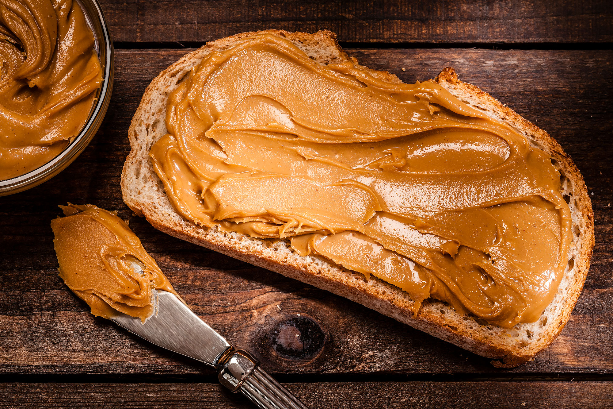 Toast with peanut butter shot on rustic wooden table