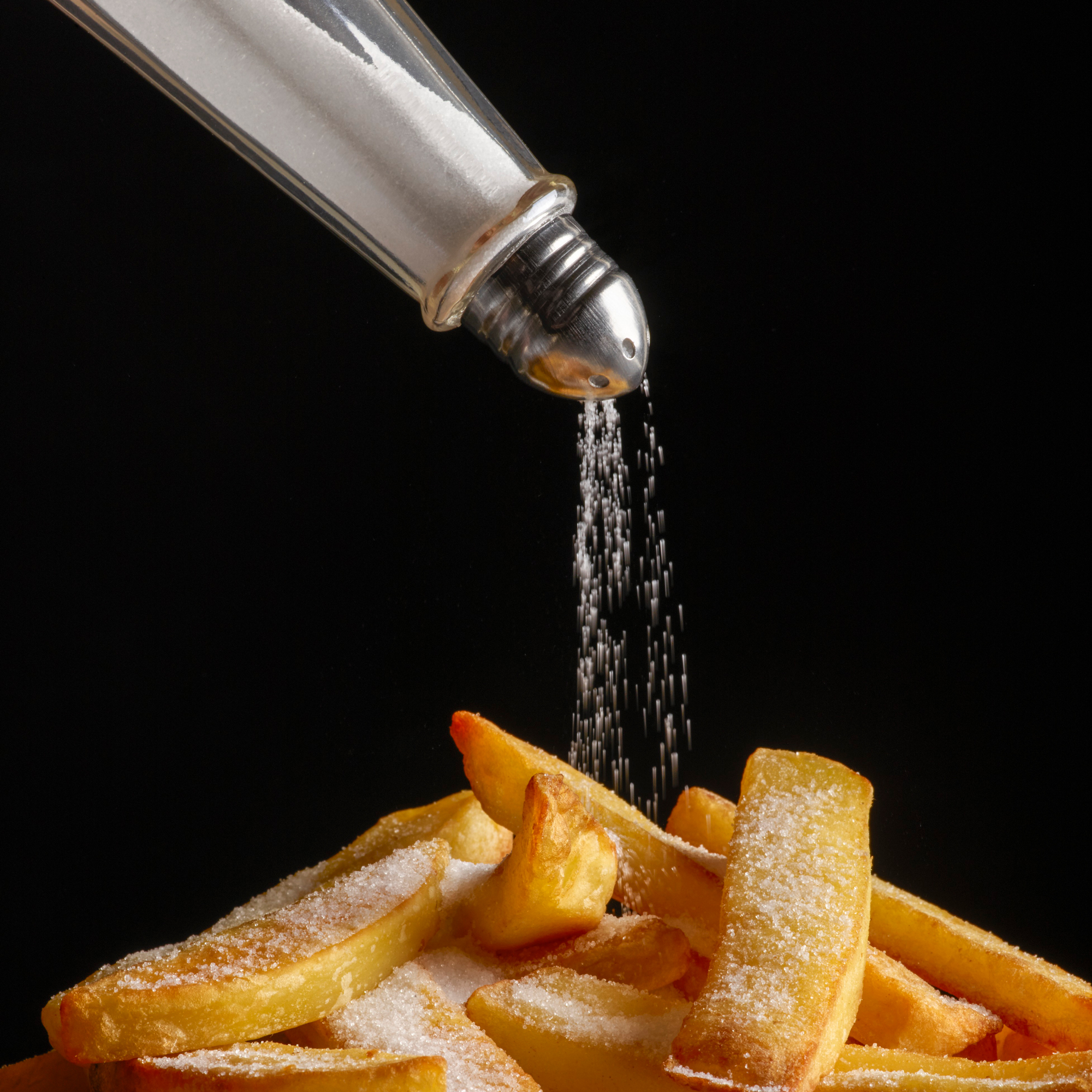 pouring salt onto French fries