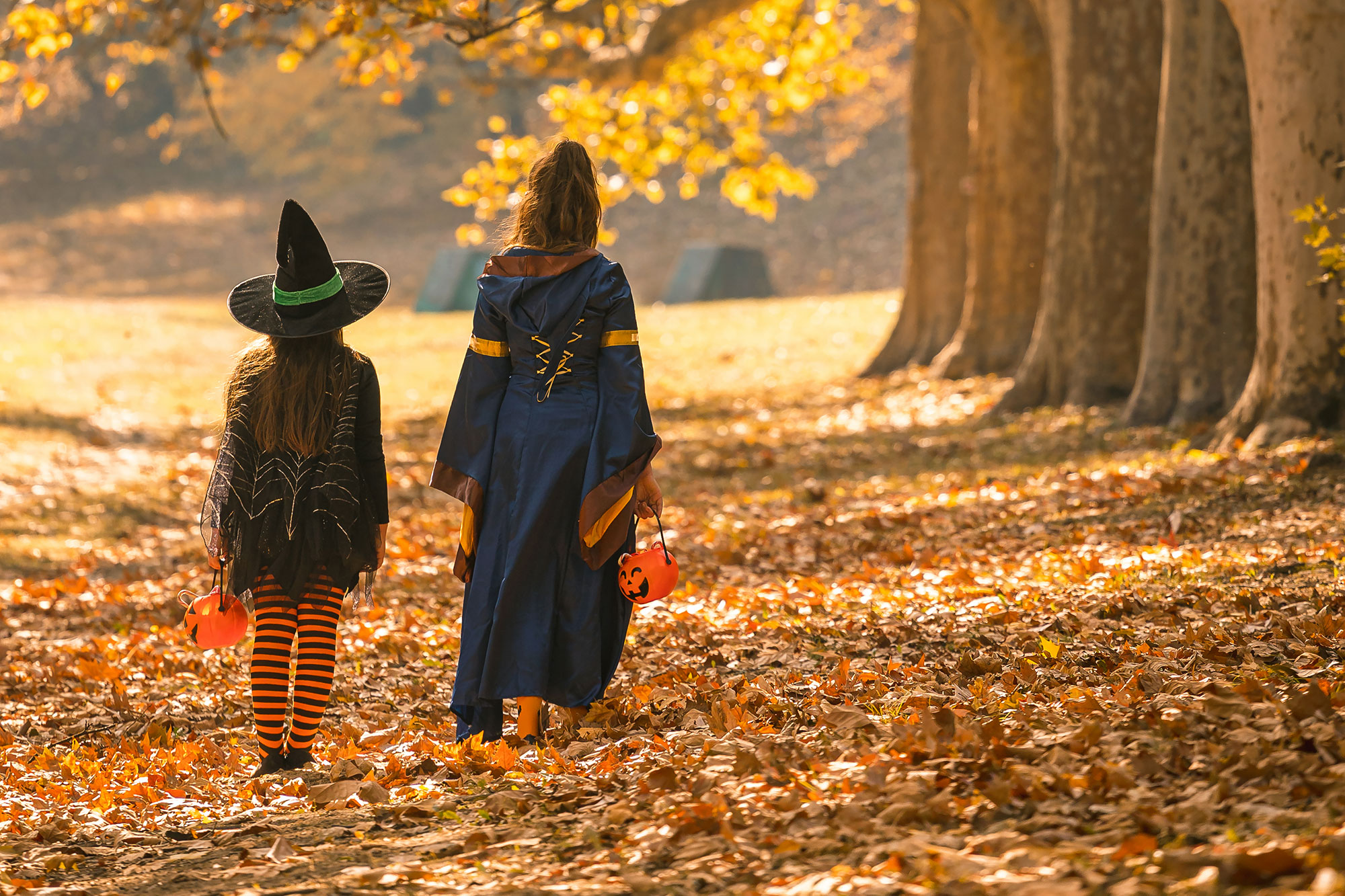 Two young girls in Halloween costumes walking through autumn woods to go trick or treating