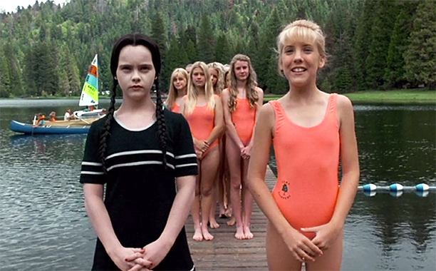 Still from Addams Family Values (1993). A group of very similar looking blonde girls in matching orange swimsuits stand on a pier in a lake. With them is Wednesday Addams, standing apart with her black hair and black swimsuit-dress ensemble.