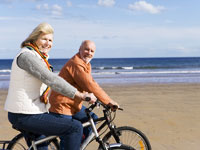 senior-couple-bicycle-beach
