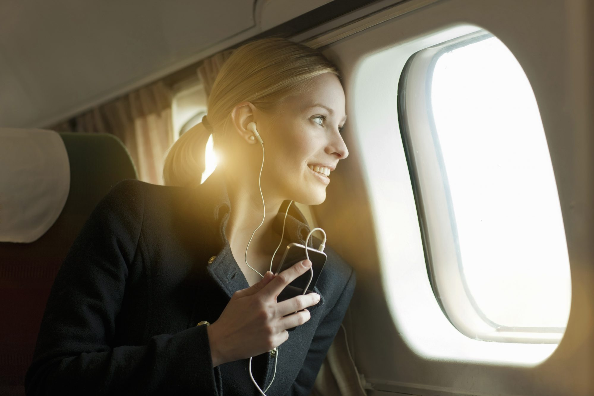 woman-headphones-traveling-podcasts-airplane-music