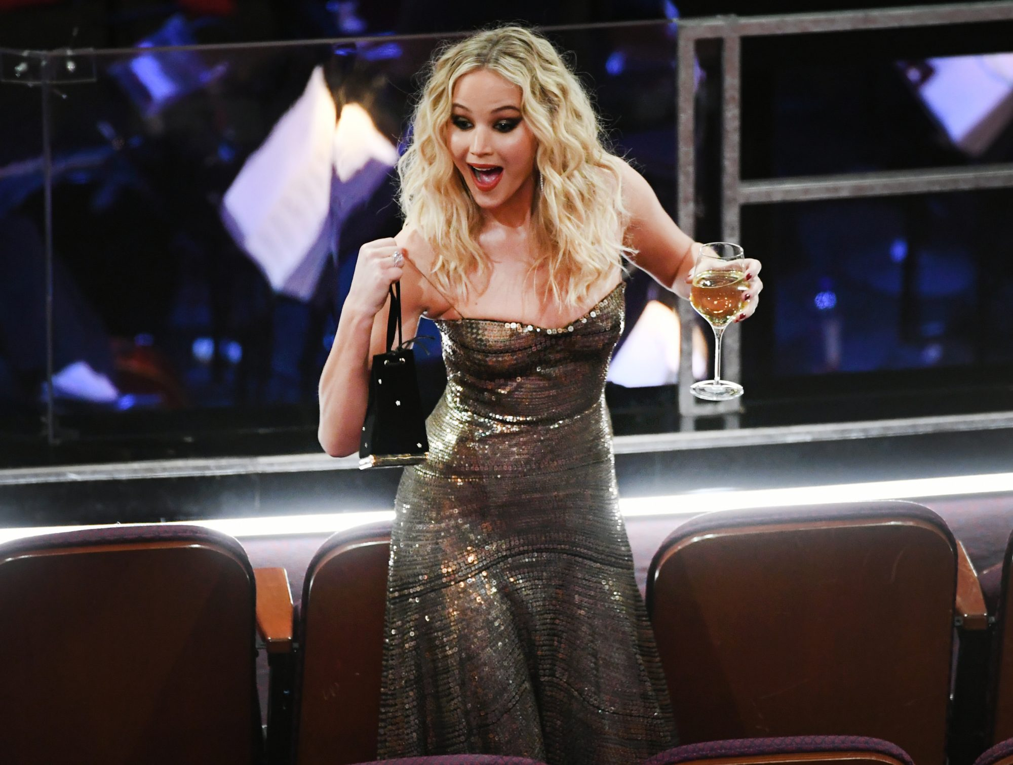 Jennifer Lawrence Climbing Over Chairs at the Oscars, Wine Glass in Hand, Is Too Relatable