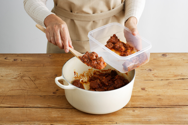 Woman spooning meat into tupperware meal prep freezer