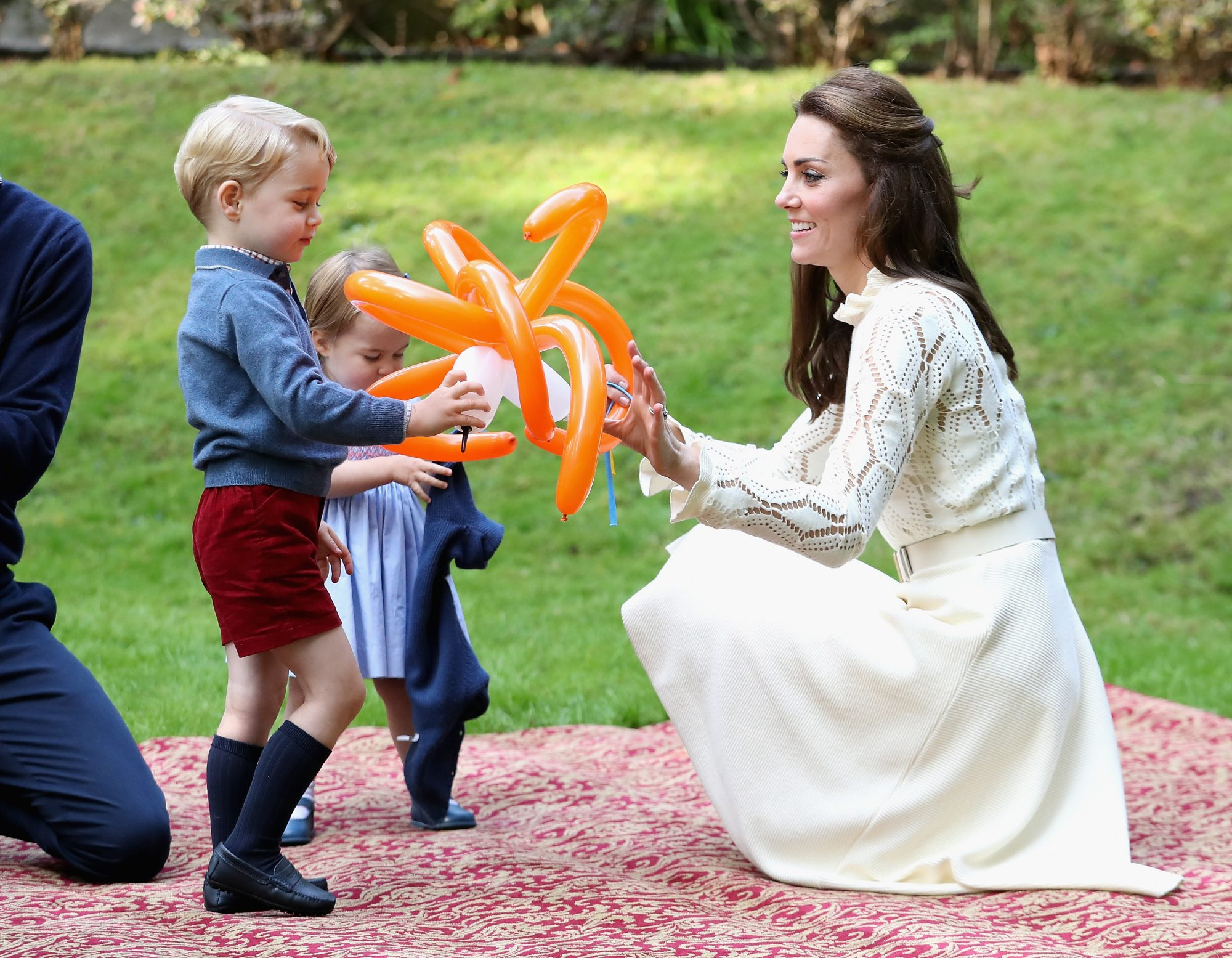 <p>George and Charlotte play with balloon animals</p>