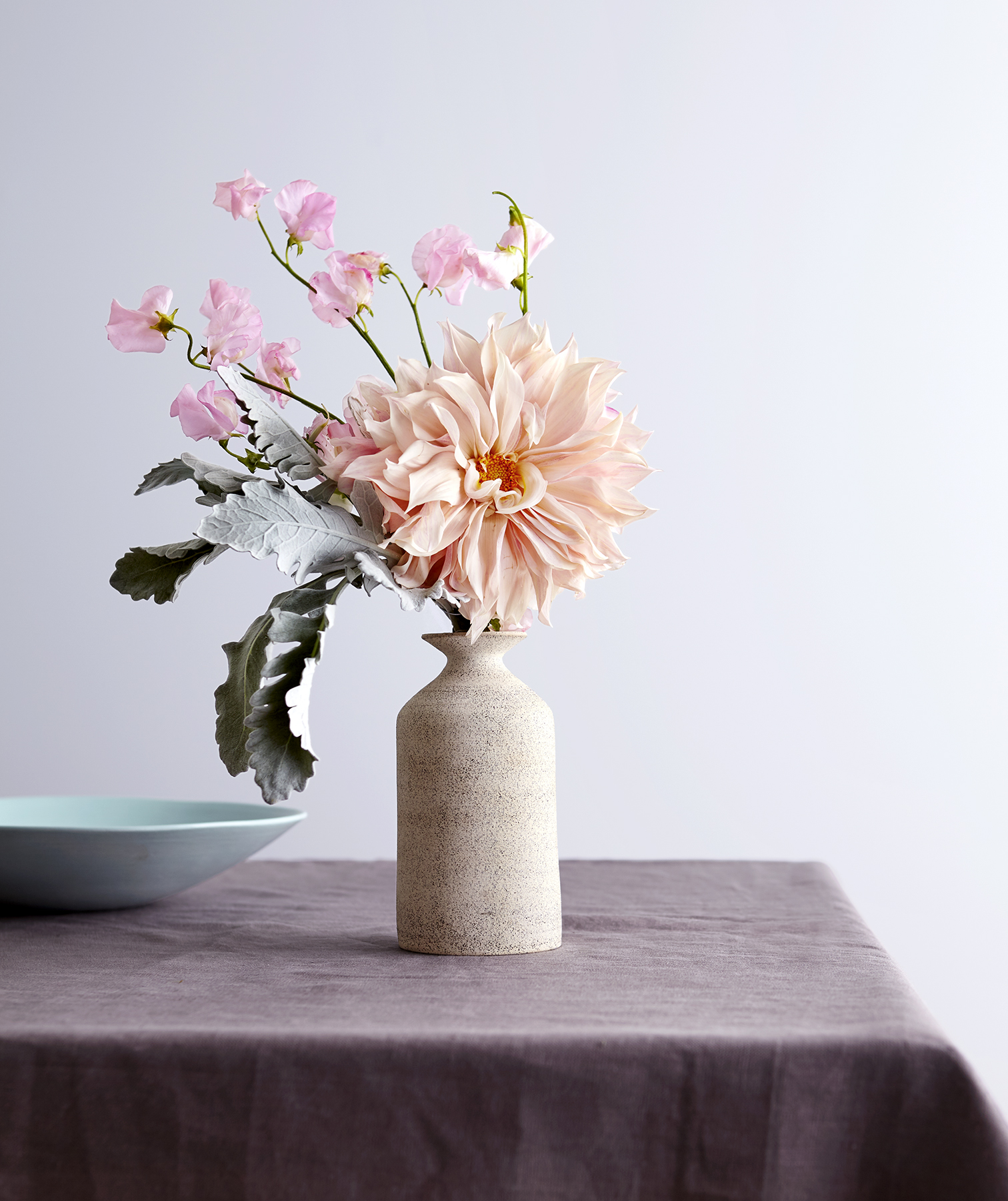 Vase with flowers, blue bowl on table