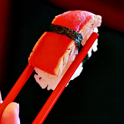 "Sushi's popularity has reached culinary celeb status throughout the world. All raw fish is generally lumped into the sushi category, but there are a variety of types based on ingredients and style. Nigiri is an oblong mound of sushi rice with a speck of wasabi that is draped with fish, and secured with a ""seaweed belt.""Recipe: Tuna Nigiri"