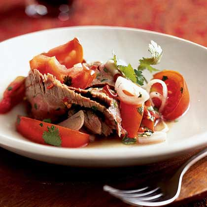 Yam Nuea Yang (Spicy Beef Salad) RecipeThis main-dish salad is hearty, yet crisp and refreshing at the same time. Ripe tomatoes sprinkled with chopped cilantro, lime juice, and red chiles add great flavor to the lean flank steak.
