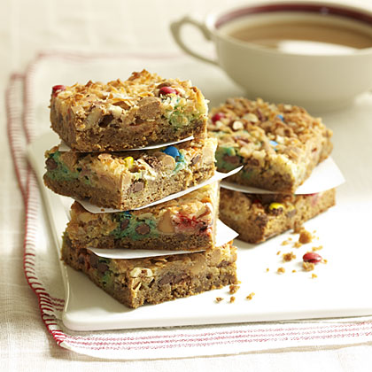 cookie bars filled with chocolate and peanut butter chips, topped with nuts and coconut