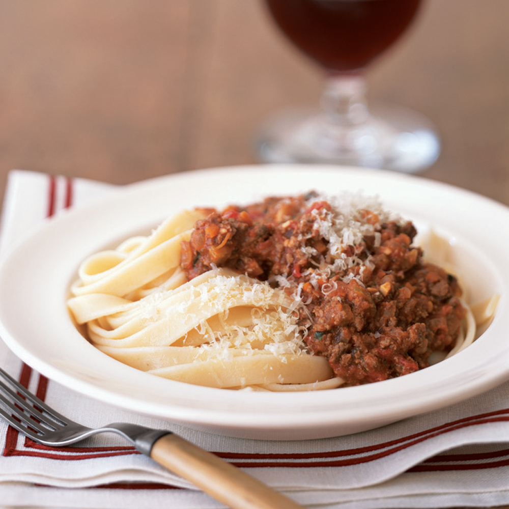 """Fettuccine with Bolognese Sauce RecipeNothing beats a rich and savory pasta sauce like this bolgonese. Start with ground beef, vegetables, and tomatoes, then build the flavor with pancetta, a little whole milk, and nutmeg. Serve with slices of garlic bread and a salad to complete your meal. One reviewer says, """"This recipe is amazing...my boyfriend thinks it's so good because I'm Italian and I learned how to make it from my mom (ha!)."""""""