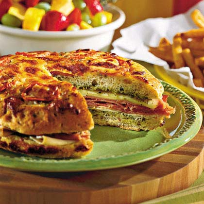 """I made this recipe for a tailgate party and it was great. I used the focaccia bread. Was a hit with everyone and deemed ""a keeper recipe""."" —rklint7149Pesto Focaccia Sandwich Recipe"