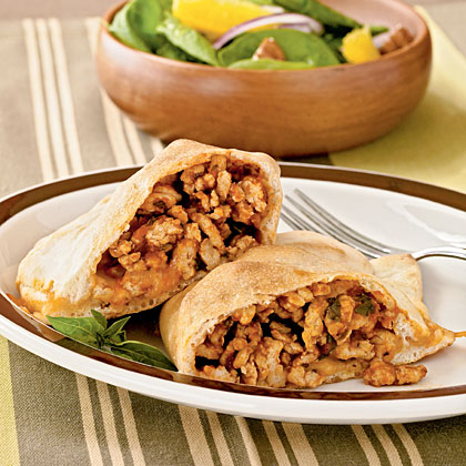 Chicken and Basil Calzones RecipeMaking calzones is easy when you start with a can of refrigerated pizza crust dough. Because this recipe features ground chicken breast in place of ground beef, it's lower in fat and calories than a traditional meat-stuffed calzone.