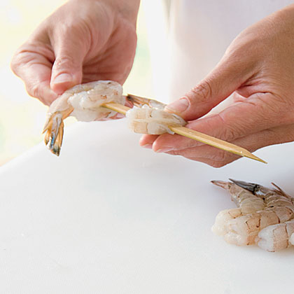 To keep them from spinning, skewer each shrimp twice—once near the head and once near the tail end. Then you can just turn the whole skewer without having to turn individual shrimp.