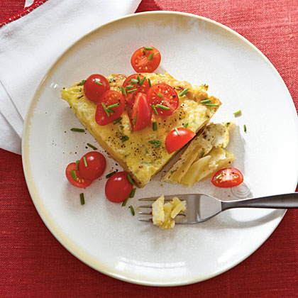 "Breakfast Tortilla RecipeIn Spain, a tortilla is a thin omelet made with potatoes, and served either warm or at room temperature. In this recipe, thin slices of potato are pressed into a pan to make a ""crust"" that holds the egg mixture, cheese, and tomatoes."