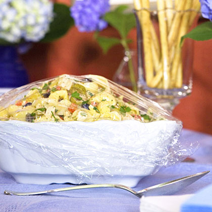 """Select a """"can't miss"""" menu that will work well for a """"bring a dish"""" party. Choose items that will travel well, hold well and require very little assembly before the party. Make sure to wrap all items carefully and store properly until serving time. Remember to ask hostesses to bring food in a white serving dish for a completely coordinated look."""