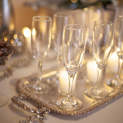 You'll need Champagne or something sparkling and festive–use whatever fits your taste and budget. Your food and beverages can pull double duty when you make them a part of your decorations, too. For example, use a pretty bowl to chill the bubbly and display beautiful glasses on a silver tray. Add a few candles and the result is elegant, shimmery, and sparkling–perfect for this party.