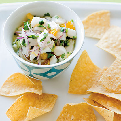 Scallop Ceviche RecipeCeviche is a popular Latin American appetizer where some type of seafood is marinated in an acid mixture, usually lemon or lime juice and combined with fresh veggies.  The action of the acid on the raw fish changes the texture of the fish to make it more firm, but it does not actually cook the fish, so be sure to use very fresh seafood.