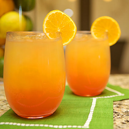 The Orange Beach RecipeEvery party needs a signature cocktail. Mix up a batch of Orange Beaches, a refreshing spin on the traditional Tequila Sunrise. Inspired by the sunset, it calls for tequila blanco, orange juice, cranberry juice, a squeeze of lime, and a little grenadine floating on top.