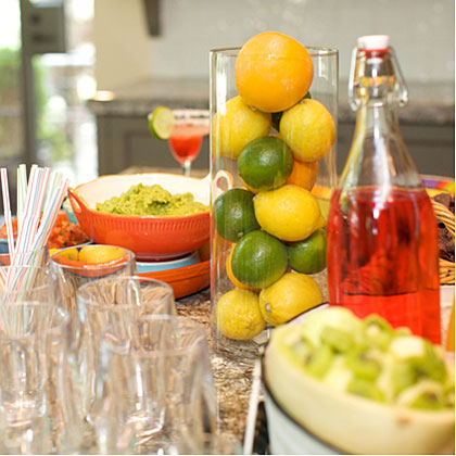 Don't worry too much about decorating. Let your self-serve bar be the star of the party. When setting up the bar, pay careful attention to the food and presentation. Group colors together and use clear serving pieces for the drinks so their colors can shine through. Take direction from your cocktails and display lemons, limes, and oranges in glass vases for pops of color throughout the party. Mix and match inexpensive colorful paper plates with your nice pieces to pull everything together.