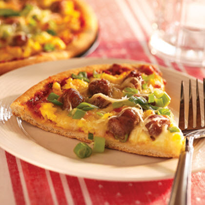 Breakfast Sausage Pizza RecipeA pancake pizza baked with layers of mozzarella cheese, sausage slices, scrambled eggs, and garnished with scallions and parmesan cheese.