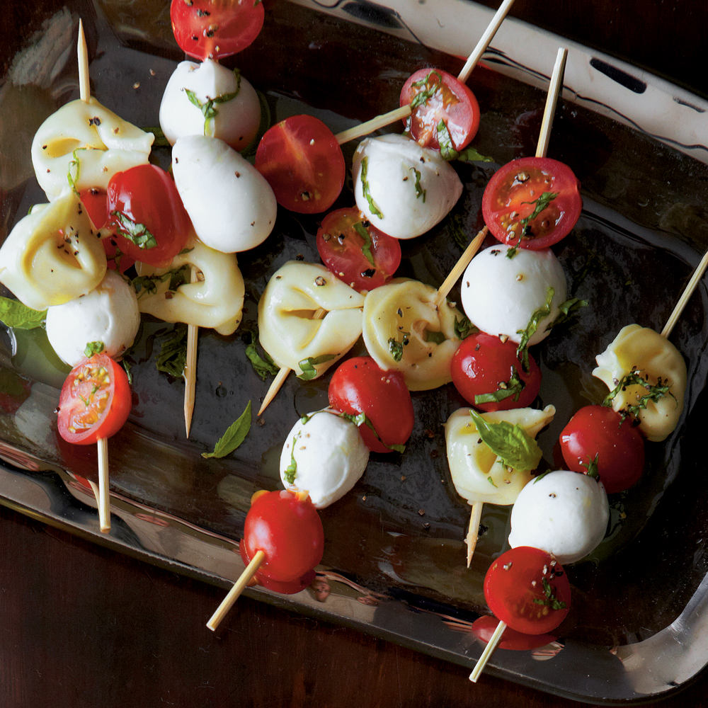 Tortellini Caprese Bites RecipeSkewer this easy lunch option before the game and serve them in a glass vase to save room on your tailgate table.