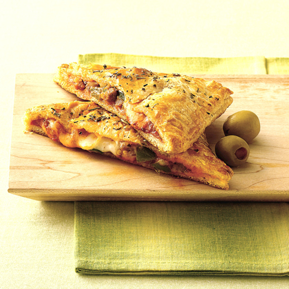 These calzone sandwiches are made with refrigerated crescent dinner rolls packed with ground meat, cheese, bell pepper and pizza sauce, served warm right from the oven.