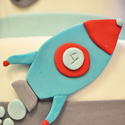 Crafting a too-cute rocket for the birthday cake is easy when using fondant. You can purchase pre-made fondant at most major craft stores in various colors. Break out the slicing tools and get creative!