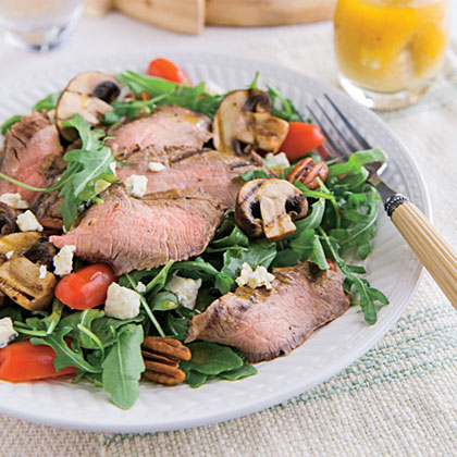 Grilled Portobello-Flank Steak Salad with Blue Cheese Vinaigrette RecipeTangy blue cheese, spicy arugula, scrumptious steak, and portobellos make Grilled Portobello-Flank Steak Salad with Blue Cheese Vinaigrette an undeniable winner.