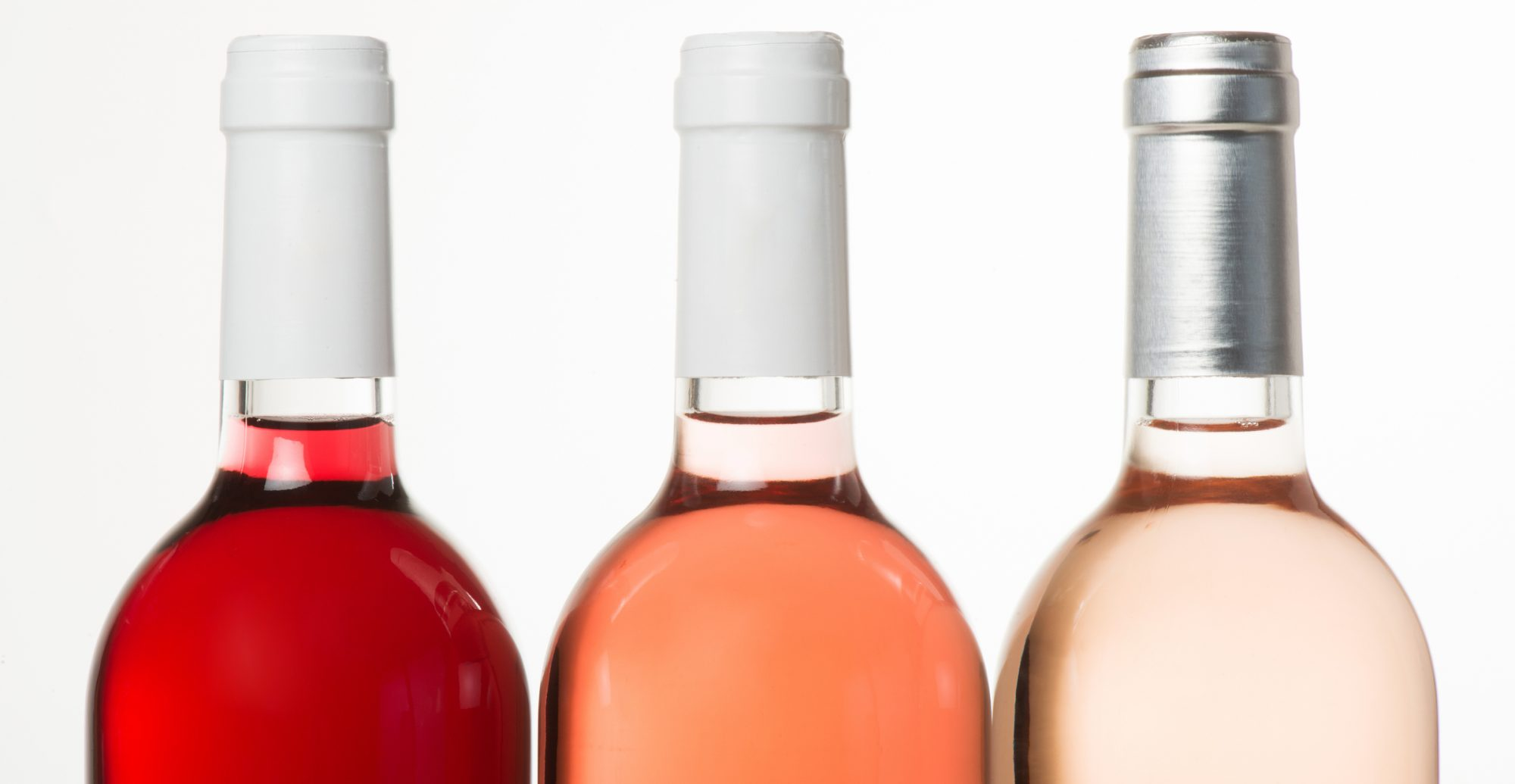 Tree colors of Rose wine in bottle, isolated on white