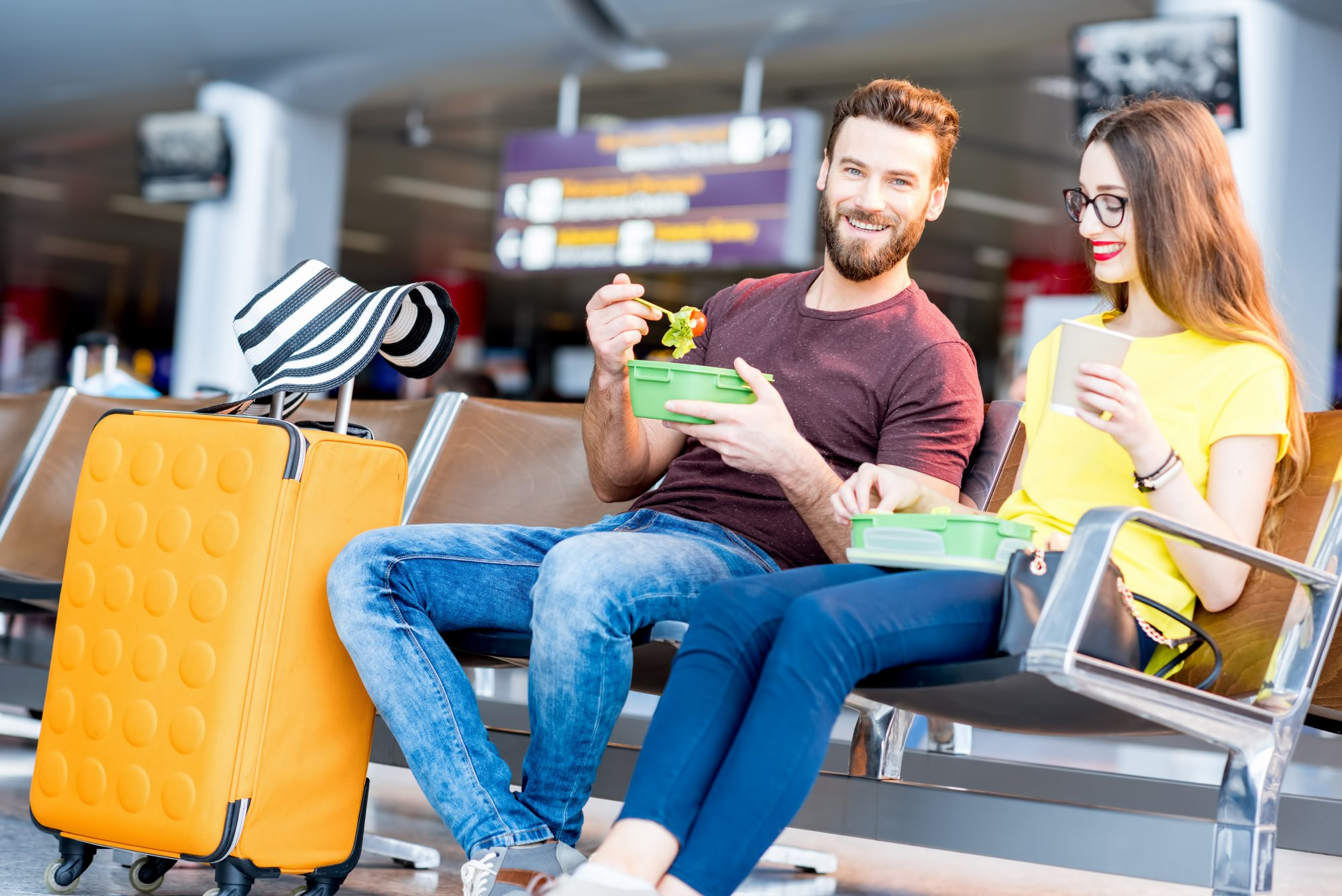 <p>Young couple having a snack with lunch boxes at the waiting hall of the airport during their vacation</p>