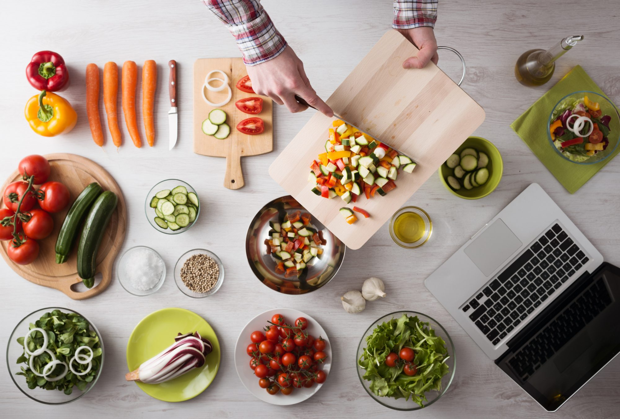Man's hands cooking at home and chopping fresh vegetables on a cutting board, kitchen tools and food ingredients all around, top view