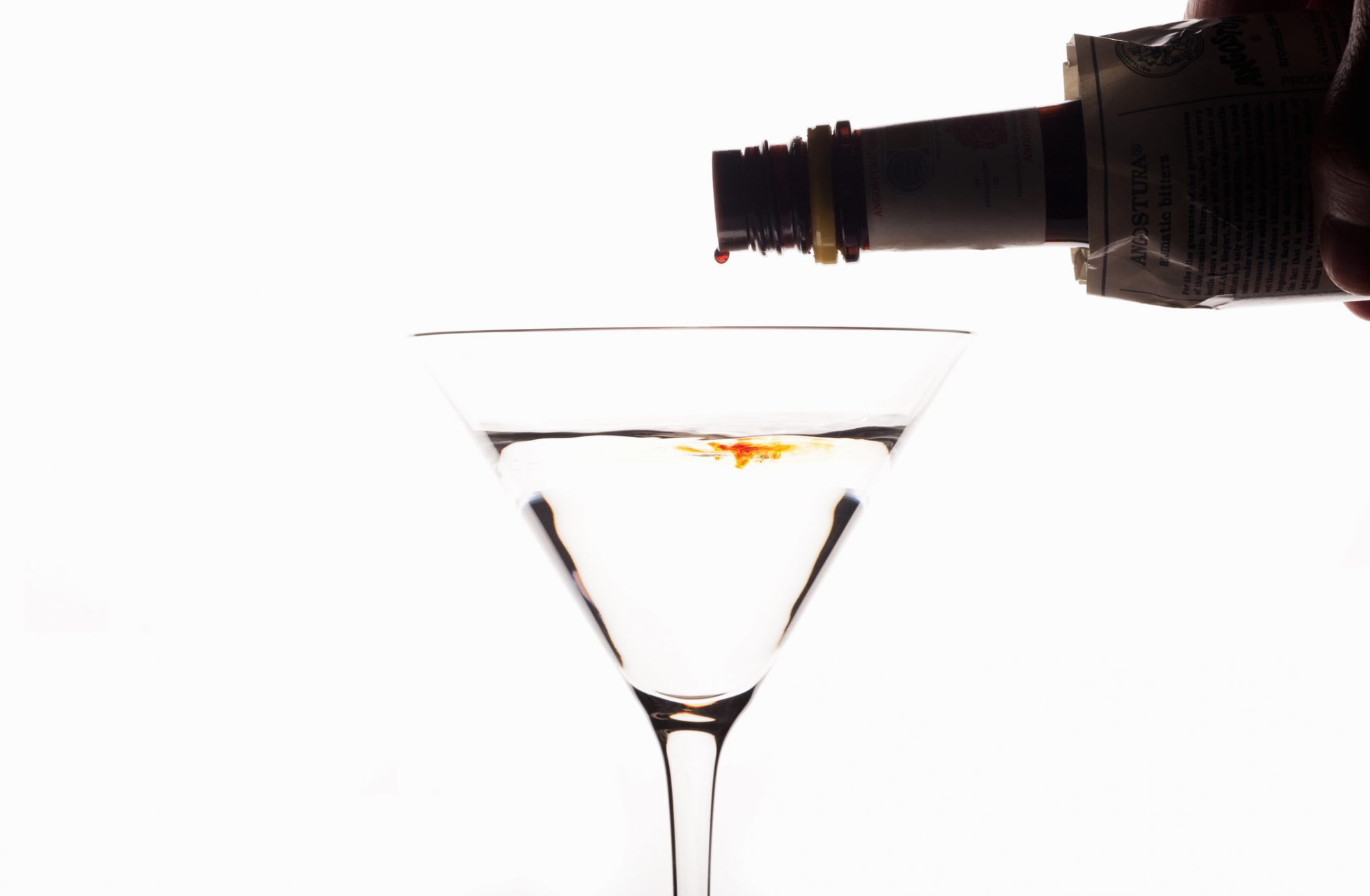 <p>Angostura Bitters being poured into a Cocktail on a white backlit background</p>