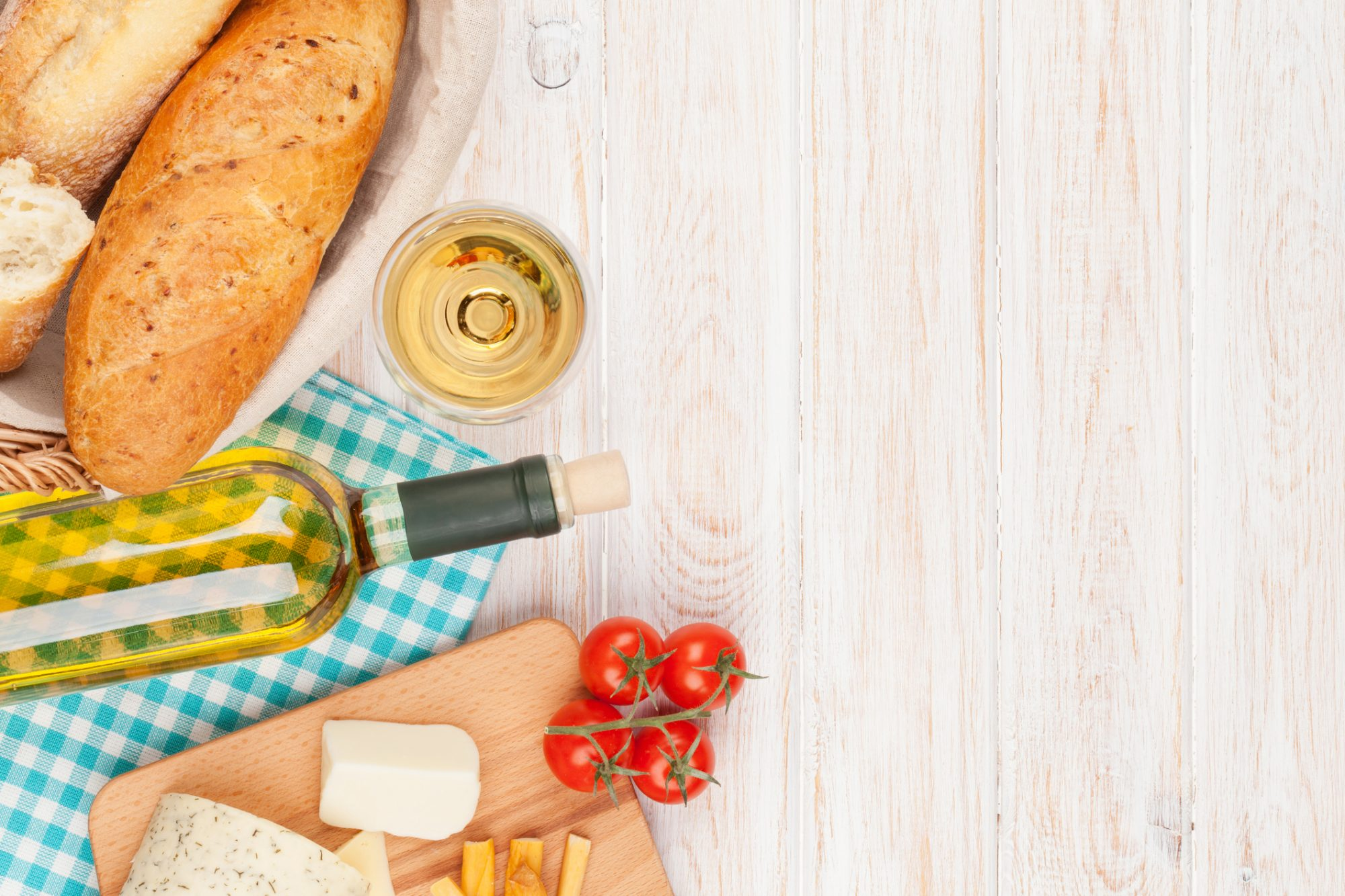 <p>White wine, cheese and bread on white wooden table background with copy space</p>